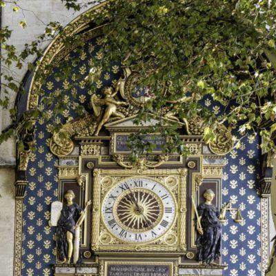 Fabuleux mécanisme et chef d'œuvre d'horlogerie, cette horloge de 47 mètres de long surplombe le Quai de l'Horloge, face à la Seine. Malgré cette situation privilégiée, l'on peut passer à côté sans la remarquer si l'on ne lève pas les yeux et c'est fort dommage ! Dotée de couleurs chatoyantes, agrémentée de multiples détails, c'est un spectacle peu commun dans la capitale. Riche d'histoire, cette horloge fut commandée par le roi Charles V en 1370 et achevée en 1372, soit il y a près de 645 ans, par un horloger de notre région, le lorrain Henri de Vic. Durant ces six siècles, les souverains de France y ajoutèrent leur touche, tant et si bien que l'Horloge que nous voyons aujourd'hui garde les traces de chacun d'entre eux. Les restaurations et les ajouts de Henri II, Henri III et Henri IV